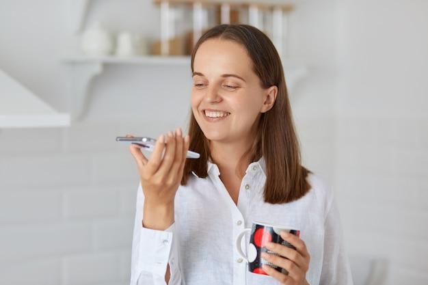 흰 셔츠를 입고 뜨거운 아침 음료를 마시고 음성 메시지를 녹음하고 커피나 차, 스마트 폰을 손에 들고 있는 긍정적인 미소 짓는 여성.