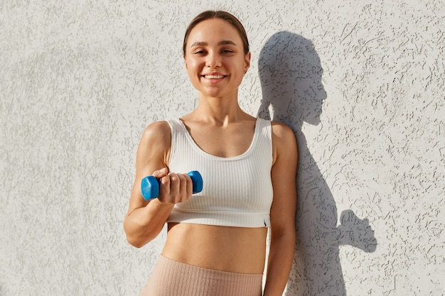 白いスポーティなトップ立っている孤立した明るい背景を屋外で身に着けている、青いダンベルを手に持って、上腕二頭筋を訓練している黒髪のポジティブな笑顔の女性。