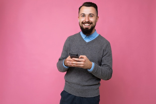灰色のセーターと青いシャツを着ている前向きな笑顔のハンサムな格好良い黒髪のひげを生やした若い男
