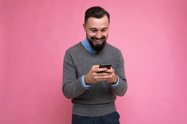 회색 스웨터와 파란색 셔츠를 입고 긍정적 인 웃는 잘 생긴 잘 생긴 검은 머리 수염 젊은 남자