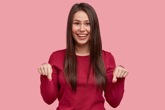 Una donna sorridente positiva con lunghi capelli scuri punta con entrambe le dita rivolte verso il basso, essendo di buon umore, consiglia di guardare il pavimento