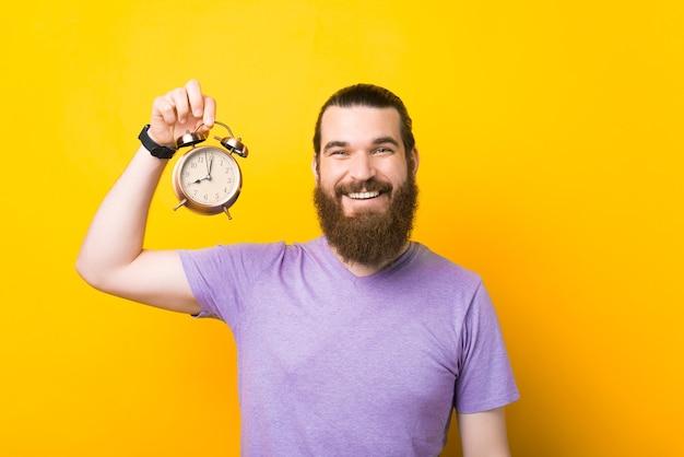 ポジティブな笑顔の男が目覚まし時計を持っています。