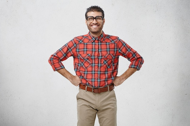 Positive smiling man keeps hands on waist, being confident in his victory