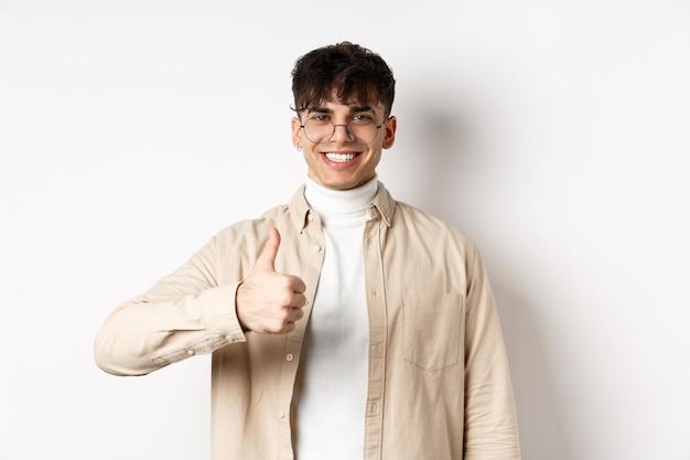Положительный улыбающийся человек показывает палец вверх и выглядит довольным, рекомендуя и одобряя вещь, довольный стоящим на белой стене.