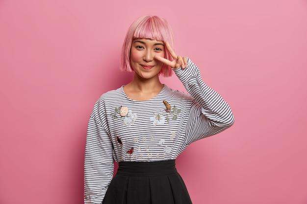 ポジティブな笑顔のピンクの髪の少女はピースサインを示し、縞模様のジャンパーと黒いスカートを着ています