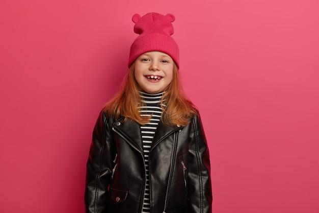 긍정적으로 웃는 빨간 머리 소녀는 긍정적으로 킥킥 웃고, 분홍색 모자와 가죽 재킷을 입고, 기꺼이 분홍색 벽 위에 격리되어 있습니다. 어린이, 스타일 개념. 사랑스러운 딸 쇼핑을 즐긴다