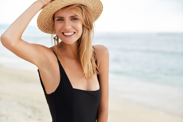 Positive smiling relaxed female with attractive appearance, wears black swimsuit, has slim perfect body.