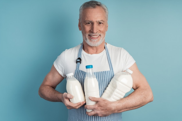 Positive, smiling, senior man holding a bottle of milk on a blue wall isolated
