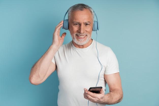 긍정적 인, 웃는 수석 남자는 그의 손에 전화를 들고 헤드폰을 착용합니다. 음악을 듣는 사람