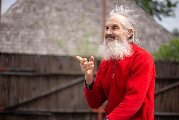 긍정적인 미소를 짓고 있는 수염 난 노인은 빨간 스웨터를 입고 자전거를 타고 바람에 머리카락을 휘날리며