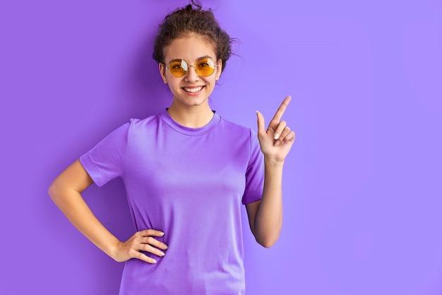 右に指を指し、左にインデックスを指すサングラスでポジティブな笑顔の十代の少女