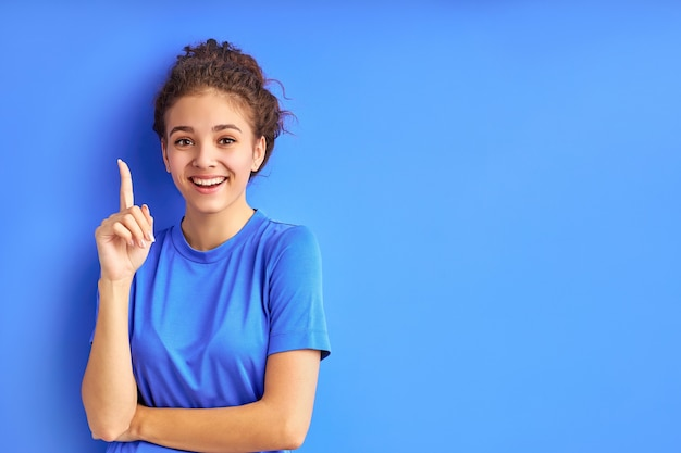 Положительная улыбающаяся девочка-подросток указывая пальцами вверх.