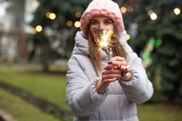 新年のツリーの近くで線香花火を楽しんでいるポジティブな笑顔の女性