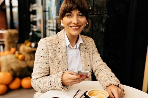 Positiva donna sorridente con i capelli raccolti che indossa una camicia bianca