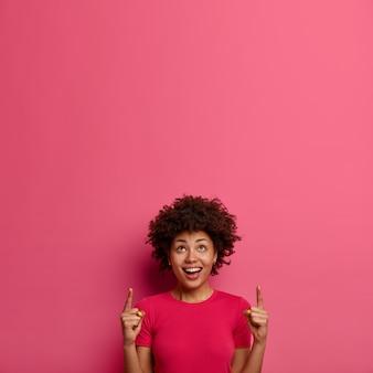 긍정적 인 웃는 젊은 아프리카 계 미국인 여자 포인트 집게 손가락 위