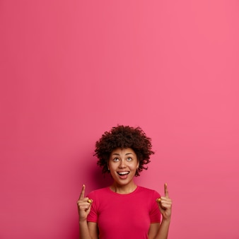 Positive smiling young african american woman points index fingers above