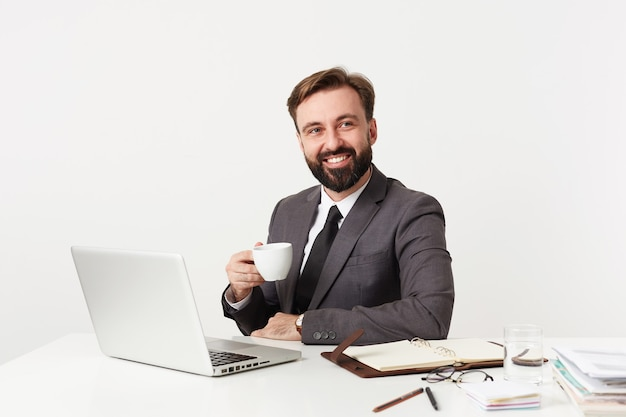 Positive smiling young bearded office worker with short brown hair sitting at table with cup of coffee in raised hand, wearing formal clothes while posing over white wall