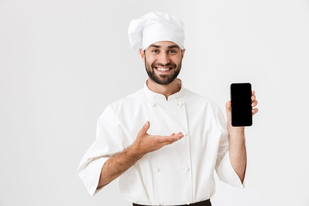 Positive smiling young chef posing in uniform holding mobile phone showing empty display.