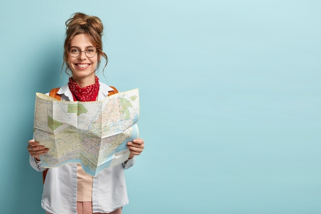 Positive smiling young female tourist searches for inspiring places, holds paper map, finds new sightseeing for discovering