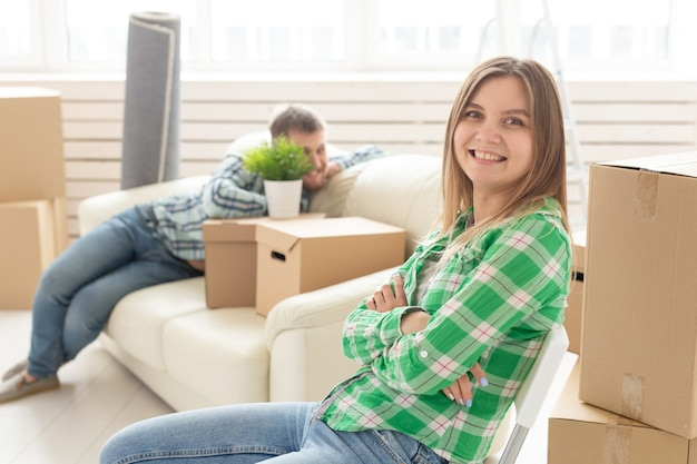 Позитивная улыбающаяся молодая девушка сидит против своего смеющегося размытого мужа в новой гостиной, пока