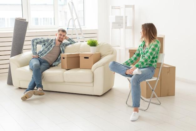 Позитивно улыбающаяся молодая девушка, сидящая напротив нее, смеется в новой гостиной, переезжая в новую