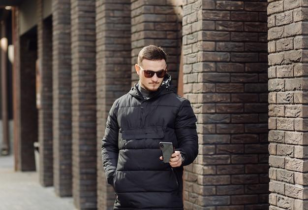 都市の建物の壁の近くに一人で立って携帯電話で話すスタイリッシュな服を着たポジティブな笑顔の若い男性