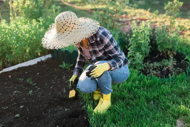 ポジティブな笑顔の若い女性の庭師は、暖かい晴れた日に春に庭のベッドに植物を植えます