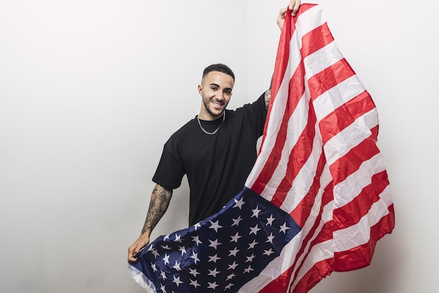Позитивный испанский мужчина с татуированными руками позирует с американским флагом, изолированным на белой стене