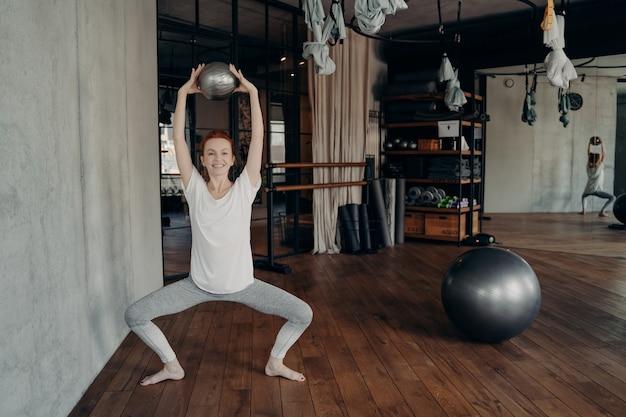 긍정적인 운동을 좋아하는 여성은 피트니스 스튜디오에서 바레 운동을 하고, 무릎을 넓게 벌린 상태에서 머리 위에 양손으로 작은 핏볼을 들고 앉아 있습니다.