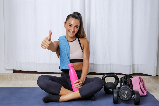Positive sportive woman showing approval sign after exercising at home