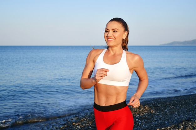 Positive sportive woman on a summer morning jogging on the beach in red leggings on the background of the sea coast close uo