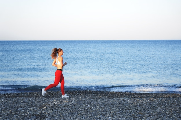 Positive sportive woman on a summer morning jogging on the beach in red leggings on the background of the sea coast