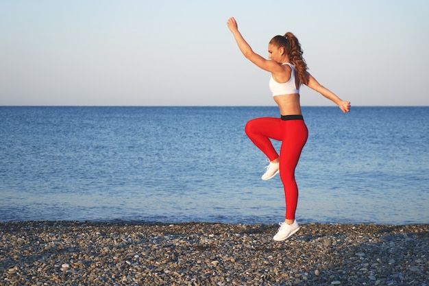 Positive sportive woman on a summer morning training on the beach in red leggings, workout on sea coast background, athlete girl jumping