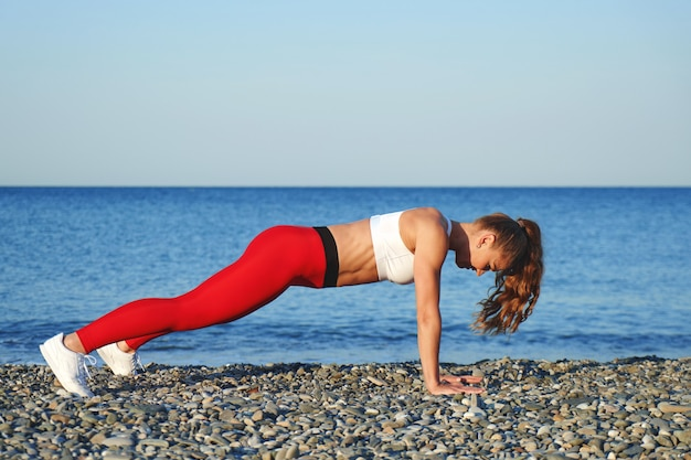 Positive sportive woman on a summer morning training on the beach in red leggings, workout on sea coast background, athlete girl in plank position