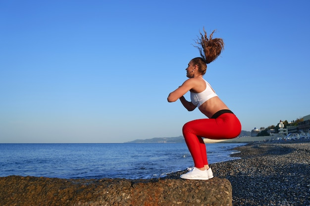 Positive sportive woman on a summer morning training on the beach in red leggings, workout on sea coast background, athlete girl squatting