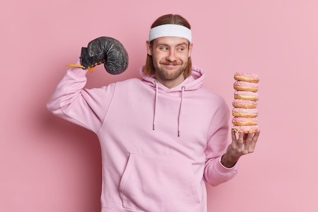 Positive sportsman raises arm shows biceps after training wears boxing glove holds pile of delicious doughnuts dressed in sweatshirt headband.