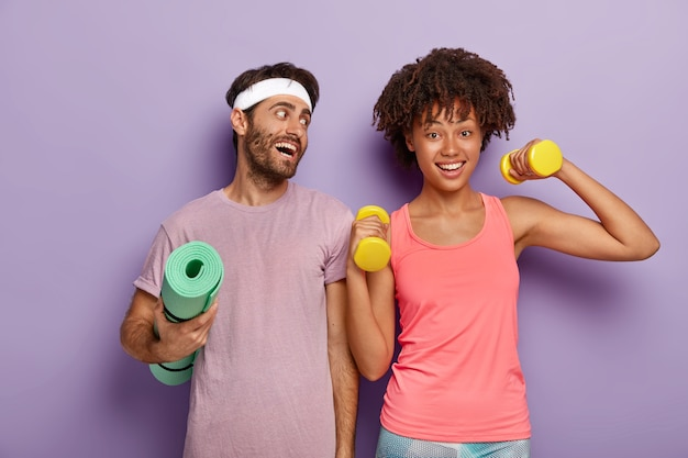 Positive sportsman wears headband and t shirt, holds crumpled fitness mat, looks gladfully at girlfriend who raises arms with dumbbells, have workout together