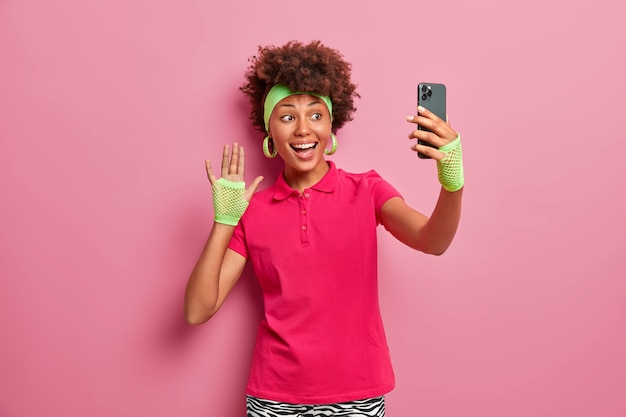 Positive sportswoman in active wear waves hand at camera of smartphone, takes selfie, sends picture to followers, has happy mood, makes greeting gesture, smiles at mobile display