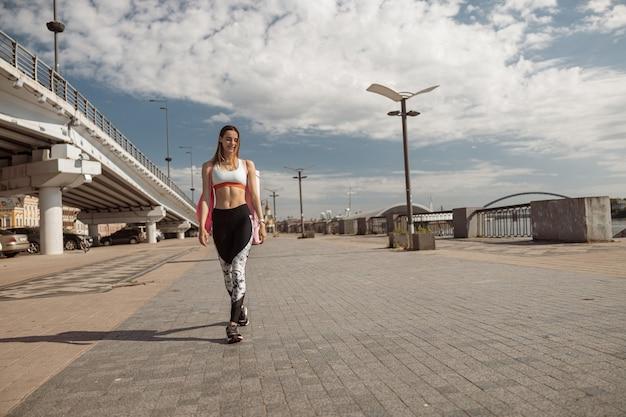 세련된 운동복을 입은 긍정적인 운동가가 대도시 해안을 따라 걷습니다.