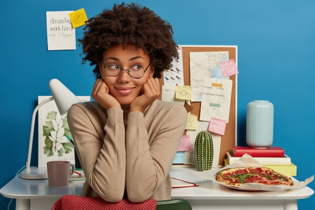 Positive student girl wears spectacles, holds cheekbones, poses in study near creative workplace with notepad, books, mug of coffee, tasty snack.
