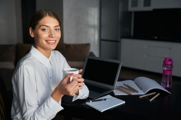 Positive student sitting at kitchen table with modern laptop