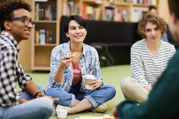 Позитивные студенты обедают в библиотеке
