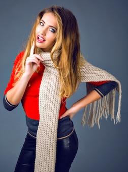 肯定的なスタジオファッションライフスタイル秋冬の肖像画、彼女のスカーフ、スマートカジュアルな服装で遊ぶ陽気なブロンドの女性。