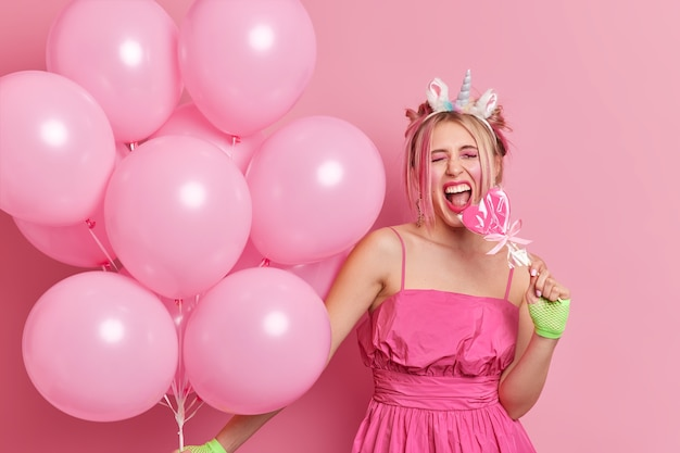 Positive stylish birthday girl has fun on party holds lollipop and bunch of air balloons wears festive dress unicorn headband