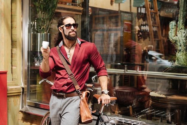 Позитивный стильный мужчина, стоящий возле велосипеда, наслаждаясь кофе