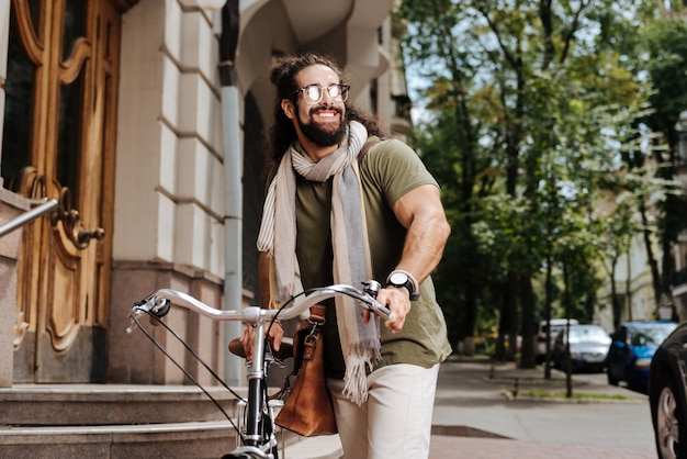 Positive stylish man wearing sunglasses while riding in the city on a bicycle
