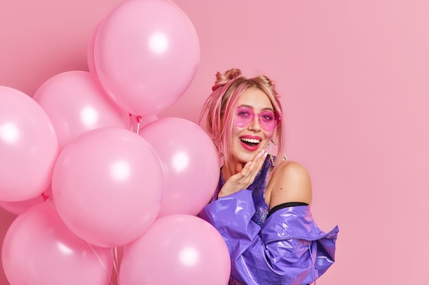 Positive stylish woman enjoys party wears trendy sunglasses purple jacket has two combed buns holds bunch of inflated balloons celebrates something