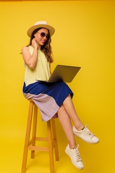 Positive stylish woman in hat and summer dress working with laptop on yellow wall