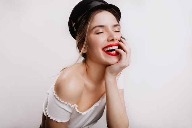 Positive stylish woman with bright lipstick laughing with her eyes closed. girl in black cap posing on white wall.