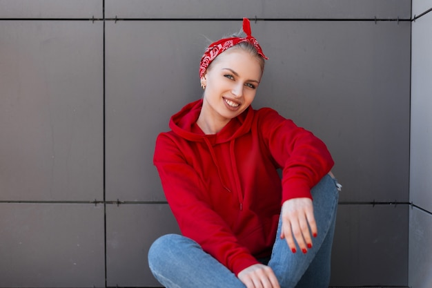 빈티지 청바지에 유행 빨간 셔츠에 빨간 두건에 헤어 스타일을 가진 긍정적 인 세련된 젊은 여성이 앉아 회색 현대 건물 근처에 미소